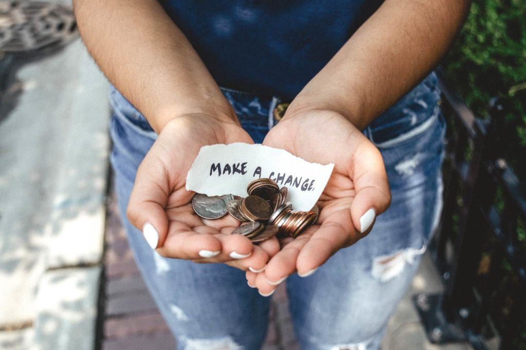 "Person holding their hands outstreched, holding change and scrap of paper that says ""make a change"". Photo by Kat Yukawa"